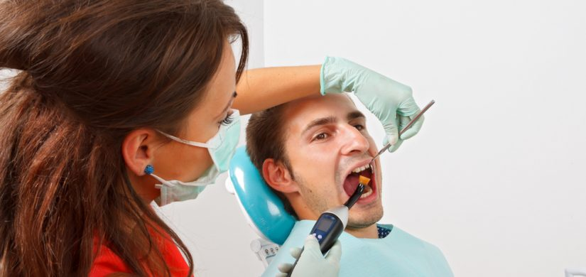 The dentist is filling the patient's tooth